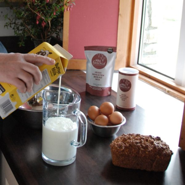 Pouring buttermilk into a jug to make wheaten bread using Wild Fuschia Bakehouse Wheaten Bread Mix